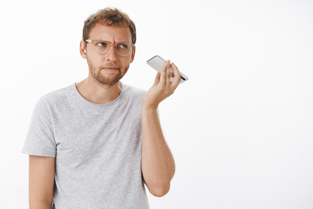 Guy listening audio message cannot understand what strange noise coming from dynamics holding smartphone near ear staring aside with intense focused expression concentrating on sound