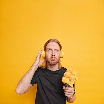 Guy listens music via headphones eats big delicious ice cream has upset expression walks during summer time focused above wears casual black t shirt isolated on yellow wall