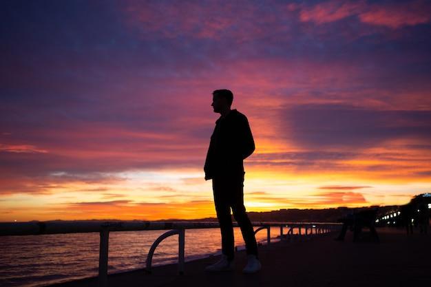 フランス、ニースの海の海岸でゴージャスな夕日を見ている男。