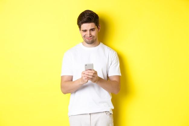 Парень недовольно смотрит на экран смартфона, читает странное сообщение по телефону, стоит в белой футболке на желтом фоне