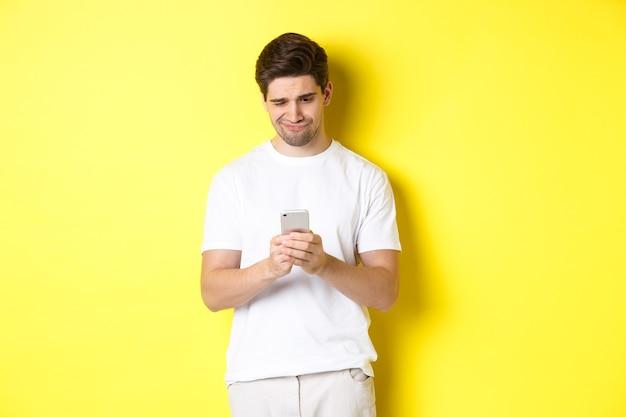 Ragazzo che guarda scontento allo schermo dello smartphone, legge uno strano messaggio sul telefono, in piedi in bianco t