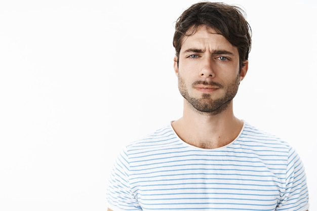 Guy looking frustrated and disappointed squinting feeling doubtful, unsure and suspicious standing confused against gray wall cannot get clue why wife acting strange over gray wall