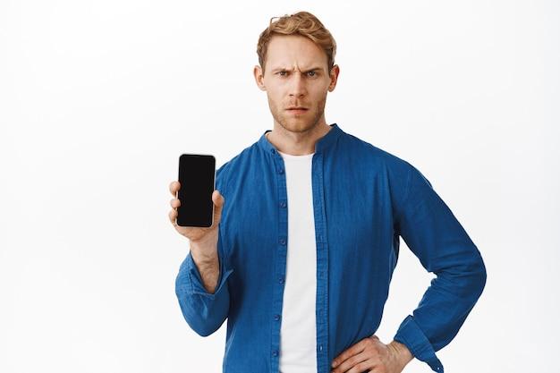 携帯電話のディスプレイで何かをデモンストレーションしている間、イライラしているように見える男、不平を言っている、白い壁
