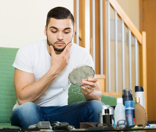 Guy looking at his problematic skin in a mirror
