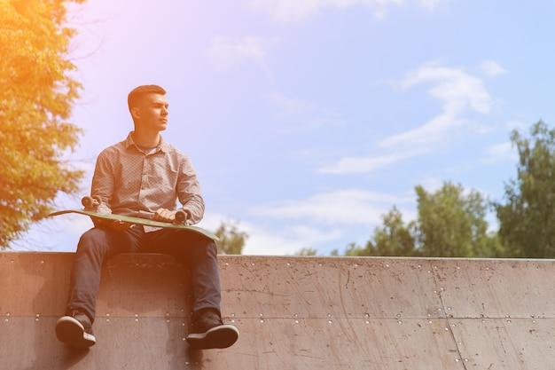 横を見て、暑い夏の日、日光の青い空の背景に公園でスケートボードのスライドに座ってスケートボードを保持している男