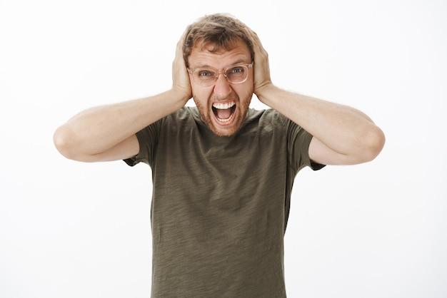 Парень теряет самообладание, злится на громкие звуки по ночам, громко кричит с выражением гнева, прикрывая уши ладонями на голове, в ярости в повседневной темно-зеленой футболке