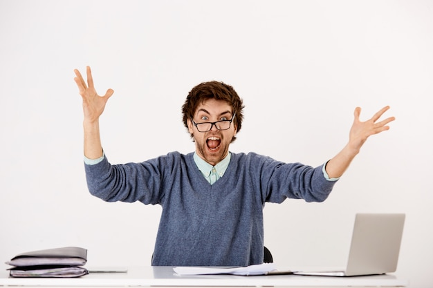 Guy losing temper at job, sit office desk with laptop and piles documents, raising hands dismay, scream annoyed and distressed