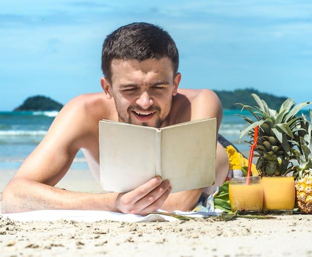 Il ragazzo sdraiato sulla spiaggia e leggendo un libro sullo sfondo dell'estate