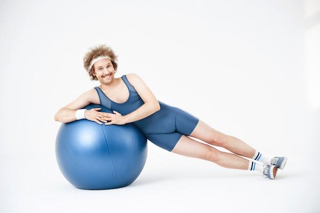 運動ボールの上に横たわる男。横になっています。手にボール