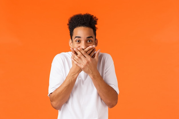 Guy made funny prank trying hold laugh. hilarious and amused african-american male in white t-shirt, giggle cover mouth with palms and staring amazed , chuckling, standing orange wall