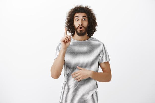 Guy ha avuto una grande idea su come risolvere il problema. ritratto del ragazzo orientale sorpreso sollevato con i capelli ricci e la barba che alza il dito indice nel gesto di eureka