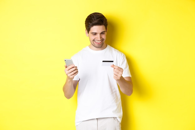 Guy making online order, register credit card in mobile application, holding smartphone and smiling, standing over yellow wall