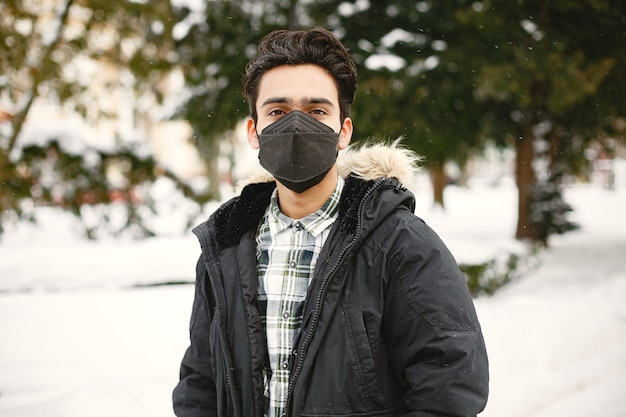Guy in a mask. indian in warm clothes. man on street in winter.