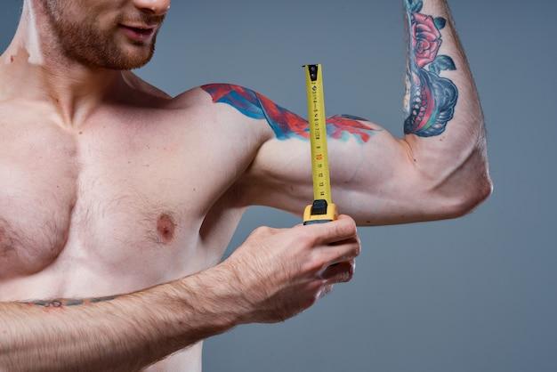 남자는 회색과 여러 가지 색의 문신 보디 빌더에 센티미터로 팔 근육을 측정합니다.