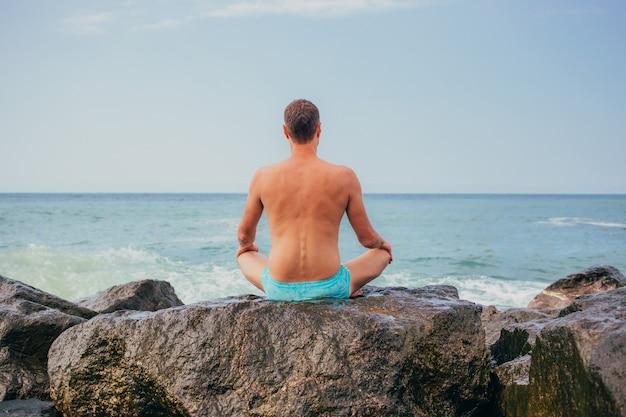 Парень медитирует на закате, сидя на скале у моря