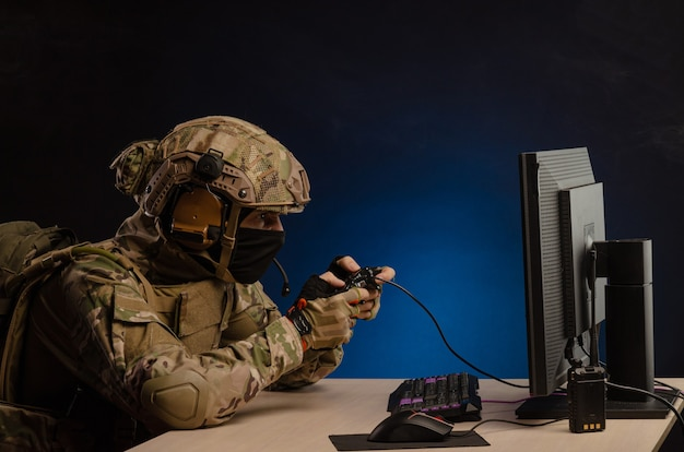 The guy in a military uniform is sitting playing computer games on a computer with a joystick