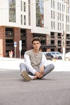 흰색 셔츠와 회색 바지를 입고 야외에서 포즈를 취하는 세련된 머리를 한 남자 모델. 트렌디한 헤어스타일은 현대적인 비즈니스 센터 근처에 있습니다. 여름날 거리에서 매력적인 남자.