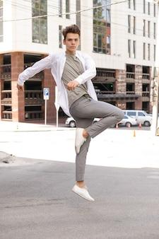 흰색 셔츠와 회색 바지를 입고 야외에서 포즈를 취하는 세련된 머리를 한 남자 모델. 트렌디한 헤어스타일은 현대적인 비즈니스 센터 근처에 있습니다. 유행 복장으로 점프하는 청년