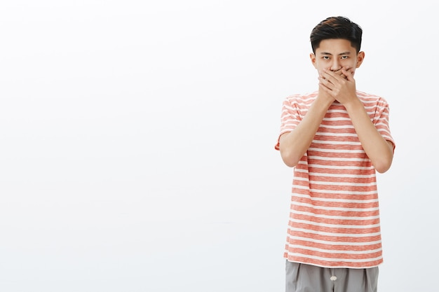 Guy not in mood to speak. portrait of serious-looking intense young asian teenager in striped t-shirt pressing palms to mouth remain speechless looking strict without no emotions