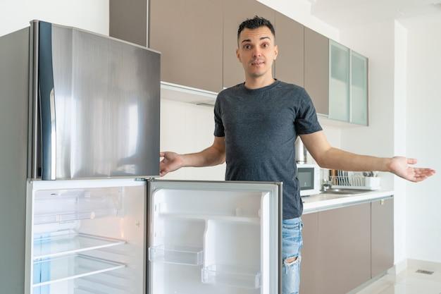 食べ物のない空の冷蔵庫の近くの男