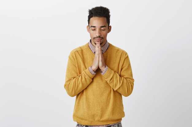 Guy needs to calm down, prepare for performance. worried attractive african-american with afro hairstyle calming down, praying with clasped palms above chin, closing eyes, hoping or wishing relaxed