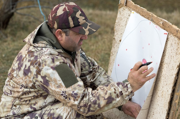The guy notes the results of shots at the target a man in camouflage shoots from cartridges