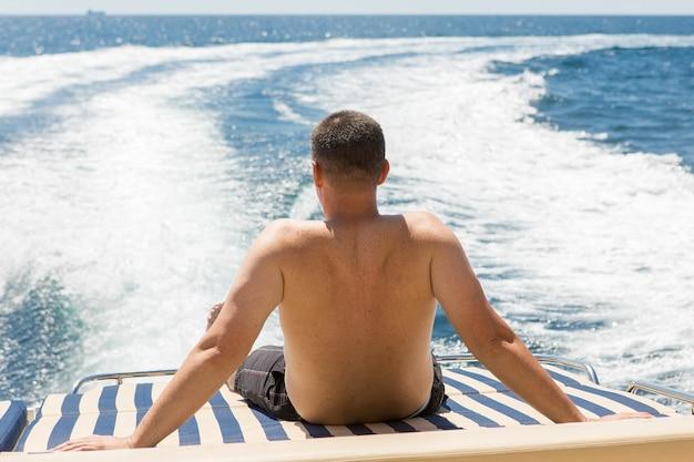 여름에 요트에 남자, 요트에 휴식, 요트의 선미에 앉다