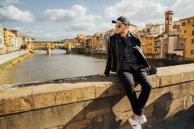 イタリア、フィレンツェ、ヴェッキオ橋の前の橋の上の男。