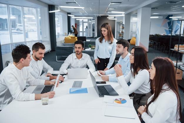 Парень с левой стороны разговаривает, коллеги слушают его. группа молодых фрилансеров в офисе разговаривают и улыбаются