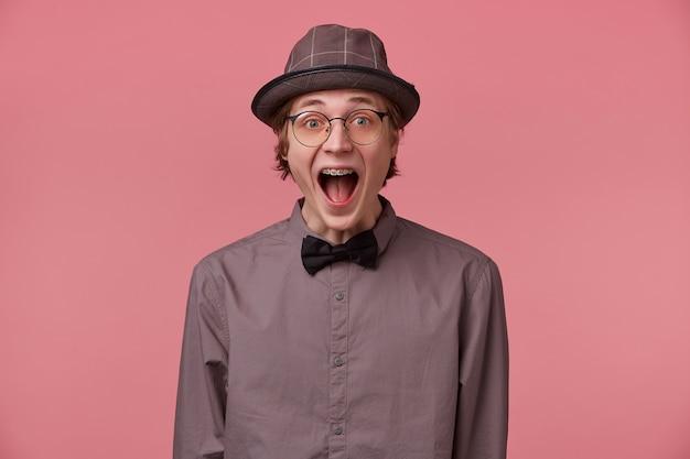 Ragazzo ha aperto la bocca per la sorpresa, è sopraffatto da emozioni positive felicità gioia non crede nel suo successo, fortuna, vestito con camicia cappello e occhiali a papillon nero ha parentesi isolate sul rosa