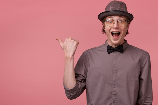 Guy opened his mouth in surprise, is overwhelmed with positive emotions happiness joy pointing thumb to the leftside draws attention dressed in shirt hat bowtie glasses has brackets isolated on pink