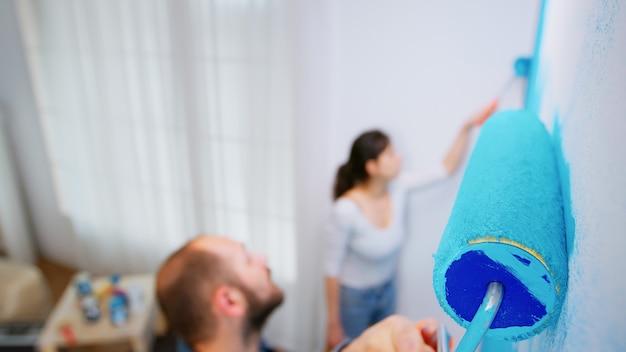 アパートのリビングルームでローラーブラシで壁を塗る男。家の装飾、建設、青いペンキ。改装と改善中のアパートの改装と住宅建設。