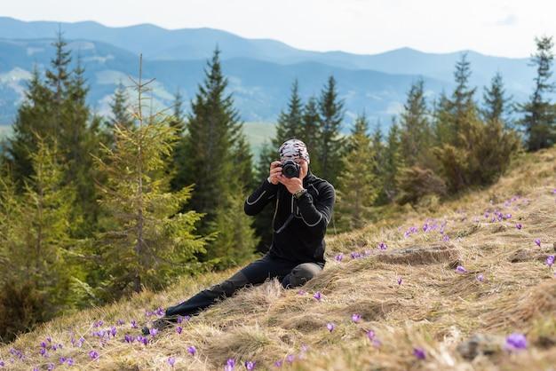 観光服装の男の写真家が開拓地にあり、クロッカスの花を撮影