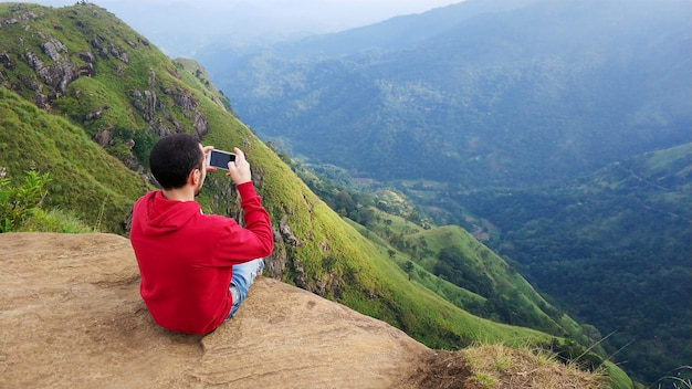 A guy photographs a mountain landscape sitting on the edge