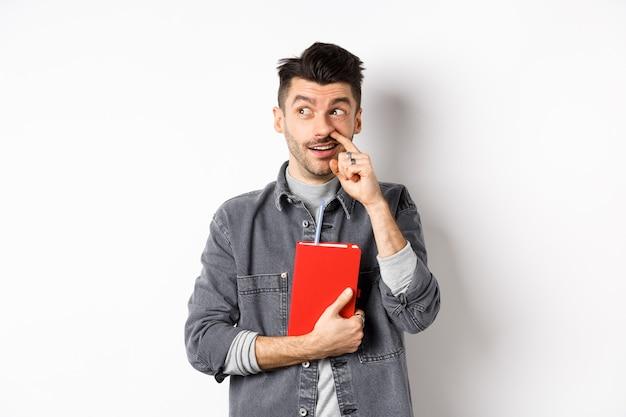코를 따고 로고를 옆으로 쳐다보고 빨간 책이나 플래너를 손에 들고 흰색 배경에 서있는 남자.