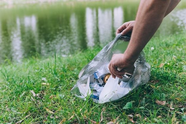 Парень собирает мусор с природы в мешок для мусора.
