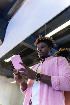 Guy in pink shirt carrying pink smartphone and checking social media