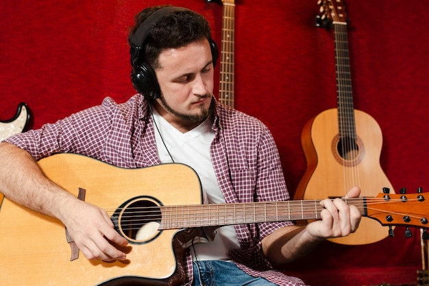 スタジオでアコースティックギターを弾く男