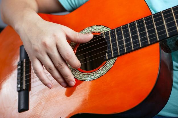 アコースティック6弦ギターを弾く男。楽器のクローズアップ演奏を学びます。