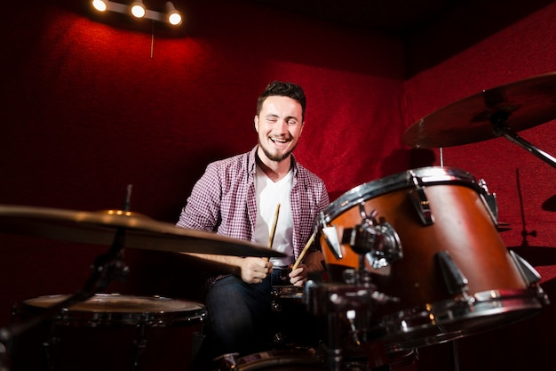 Guy playing drums and being happy