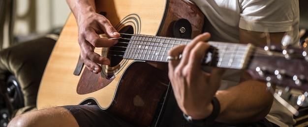 Парень играет на акустической гитаре