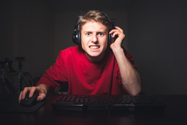 Guy playing video games on computer, concentrated face looking into the computer screen