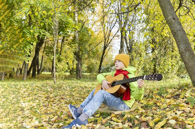 Guy plays guitar in autumn park child learns to play acoustic guitar outdoors autumn melancholy