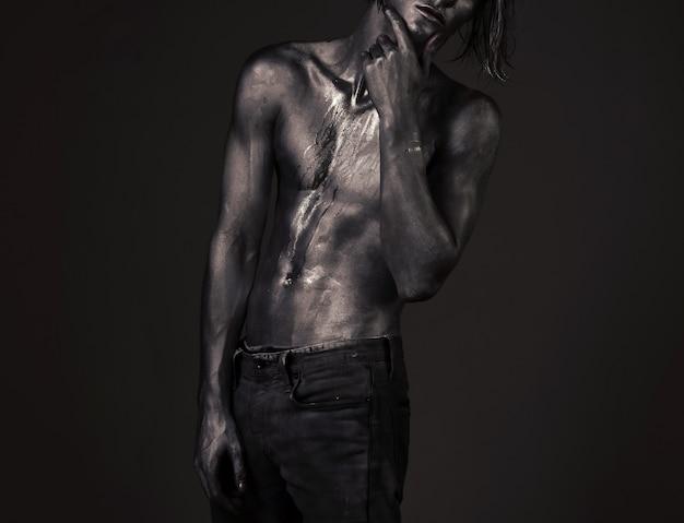잠겨있는 표정으로 포즈를 취하는 남자. 패션과 남성 성 개념. 벌거 벗은 가슴에 땀이나 페인트가 흐르는 남자, 누드 몸통은 반짝이는 은색으로 덮여 있습니다.