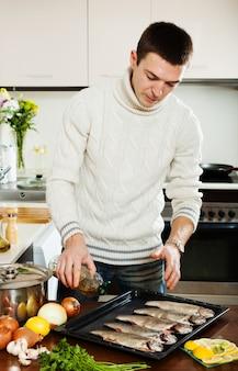 Парень наливает масло в сырую рыбу на сковороде