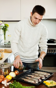 Guy pouring oil in raw fish on roasting pan