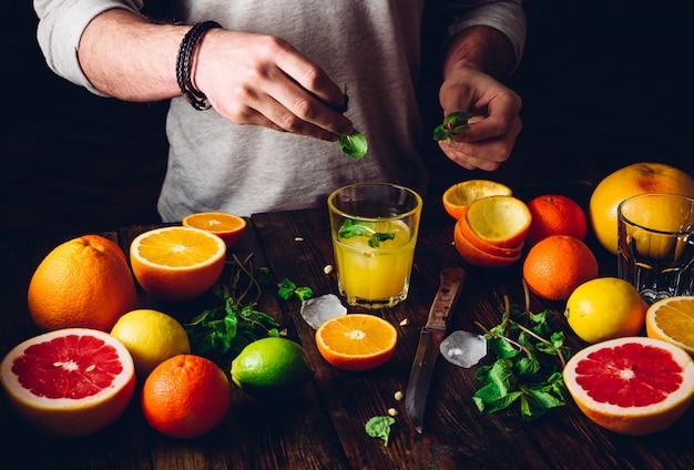 Guy prepare the citrus cocktail