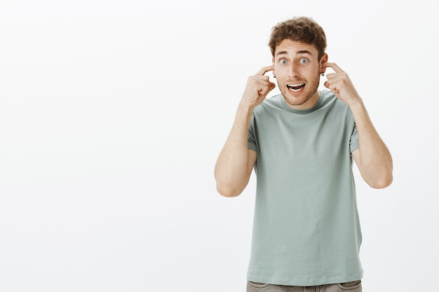耳を覆って騒音を聞かないビッグバンの準備をしている人。カジュアルなtシャツを着た興奮している面白いヨーロッパの男性学生