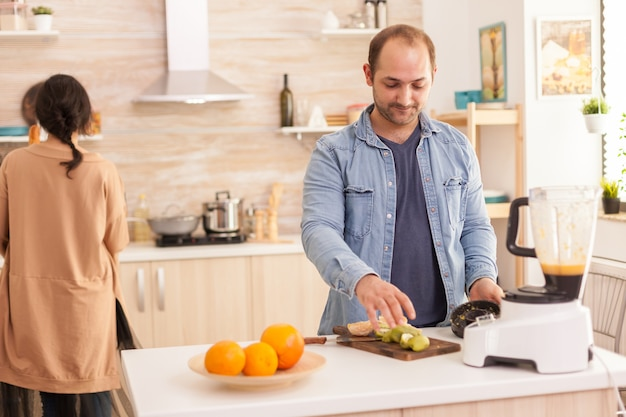 믹서기를 사용하여 부엌에서 맛있는 스무디를 준비하는 남자. 건강하고 평온하고 쾌활한 생활 방식, 다이어트를 먹고 포근하고 화창한 아침에 아침 식사를 준비합니다.