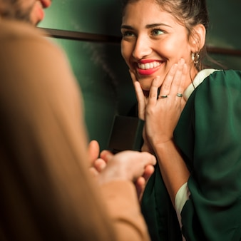 Guy presenting gift in box to attractive happy lady